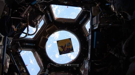 "The children's book ""The Wizard Who Saved the World"" by Jeffrey Bennett floats inside the International Space Station's Cupola observation deck with the Earth serving as a stunning backdrop. The book is one of five on the station for the Story Time From Space educational project."