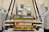 The Optical Payload for Lasercomm Science (OPALS) instrument is hoisted onto a shipping pallet for transfer to Kennedy Space Center in Florida. From there it will launch to the International Space Station.