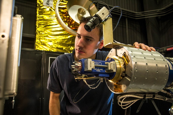 Alex Janas, RROxiTT lead roboticist, stands with the Oxidizer Nozzle Tool, part of a new technology developed to help extend the life of satellites in space.