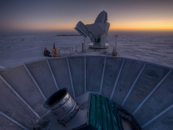 The sun sets behind BICEP2 (in the foreground) and the South Pole Telescope (in the background) in this stunning space wallpaper.