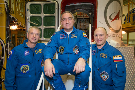 In the Integration Facility at the Baikonur Cosmodrome in Kazakhstan, NASA astronaut Steve Swanson (left) and Alexander Skvortsov (center) and Oleg Artemyev of Roscosmos pose for pictures in front of their Soyuz TMA-12M spacecraft March 21, 2014 ahead of a March 25 launch.