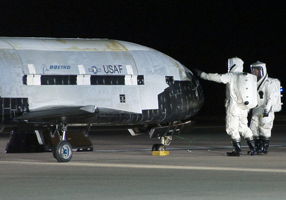 An X-37B robotic space plane sits on the Vandenberg Air Force base runway during post-landing operations on Dec. 3, 2010. Personnel in self-contained protective atmospheric suits conduct initial checks on the robot space vehicle after its landing.