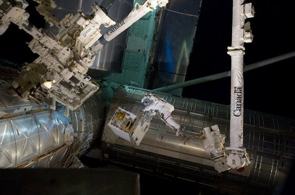 Spacewalking astronauts transfer the RRM to a temporary platform on the ISS in July 2011.