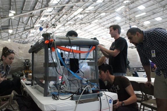 The UCSD students practice running their experiment in NASA's hanger at Ellington Field in Houston on April 9, 2014.