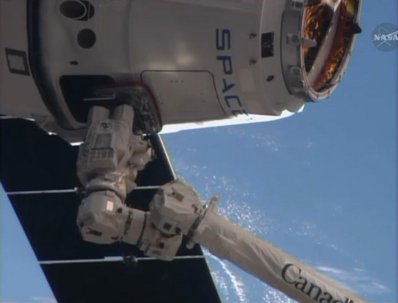 A SpaceX Dragon cargo ship is captured by astronauts using the robotic arm on the International Space Station in this close-up camera view from the outpost on April 20, 2014. The Dragon capsule delivered nearly 5,000 lbs. of supplies to the space station crew, the third such SpaceX flight for NASA.
