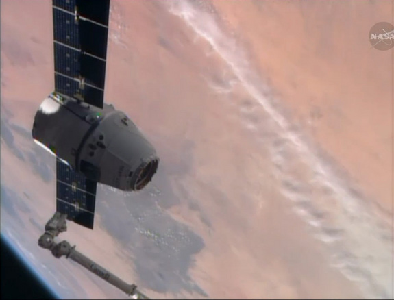 A SpaceX-built Dragon cargo ship floats near the end of the International Space Station's robotic arm, with the Earth as a backdrop, in this view from a station camera captured on April 20, 2014. The Dragon cargo ship delivered nearly 5,000 lbs. of supplies to the space station.