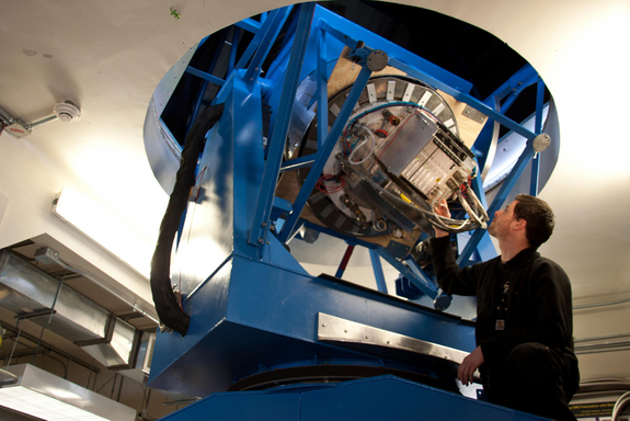 Graduate student Justus Brevik tests electronics inside of the BICEP2 telescope.