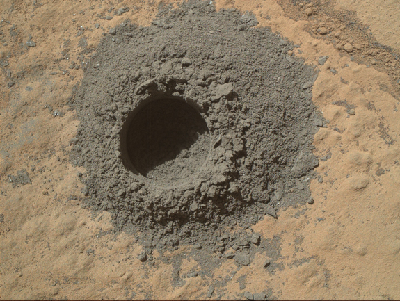 "NASA's Curiosity Mars rover completed a shallow ""mini drill"" test April 29, 2014, in preparation for full-depth drilling at a rock target called ""Windjana."" This image from Curiosity's Mars Hand Lens Imager shows the hole resulting from the test, 0.63 inch across and about 0.8 inch deep."