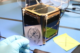 This image of the ISO Logo engraved on a Nanosatisfi satellite was taken by Nelly Ben Hayoun.