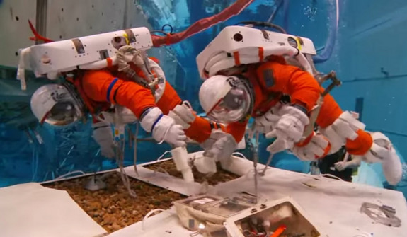 NASA astronauts Stan Love and Steve Bowen test tools and methods for exploring an asteroid in an underwater 'spacewalk' in this still from a NASA video released on May  9, 2014. The astronauts wore a modified version of NASA's orange launch and entry suits used on space shuttle missions.