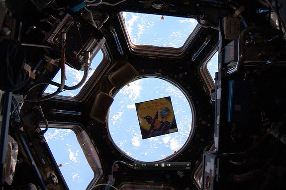 "A copy of author Jeffrey Bennett's book, ""The Wizard Who Saved the World,"" floats inside the International Space Station's multi-windowed Cupola."