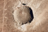 Meteor Crater, an impact crater created about 50,000 years ago when a 30-meter iron meteor struck the Earth's surface in Arizona. The giant Jupiter can redirect asteroid paths towards or away from Earth.