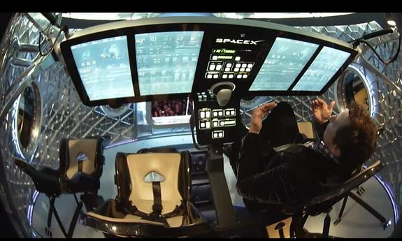 Musk narrated a portion of his unveiling inside the Dragon Version 2 spacecraft, May 29, 2014. The control panel in front of him swings up and completely out of the way for easy entrance and egress.