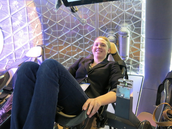 Staff writer Tanya Lewis sits inside the manned Dragon capsule on June 10, 2014.