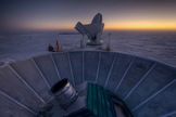The sun sets behind BICEP2 telescope in the foreground. The South Pole Telescope stands in the background.