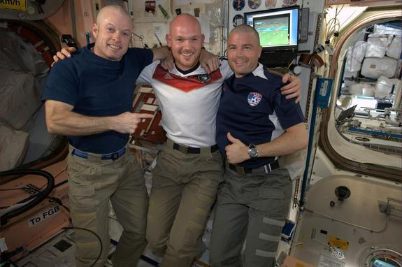 From left to right: NASA's Steve Swanson, German astronaut Alexander Gerst and NASA's Reid Wiseman line up after Gerst shaved both NASA astronauts' heads to even a bet the NASA astronauts lost after the United States lost to Germany in a World Cup match on June 26, 2014.