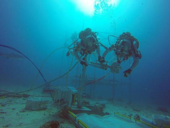 Two astronauts test out a drill that could be used in a future asteroid mission during NEEMO 18 in July 2014.