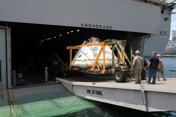 Caption: The Orion boilerplate test vehicle is loaded onto the USS Anchorage at the U.S. Naval Base in San Diego, California on July 29. A team of NASA engineers and U.S. Navy personnel will test out different techniques to haul the test spacecraft from the Pacific Ocean.