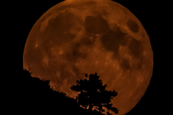 Astrophographer Tim McCord captured the supermoon rising in Washington on August 10, 2014. He caught the moon glowing red through a smoky haze.