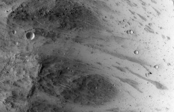 NASA's Mars Reconnaissance Orbiter snapped this view, showing the the trail left by a rolling boulder that tumbled down the side of a slope, on July 3, 2014.