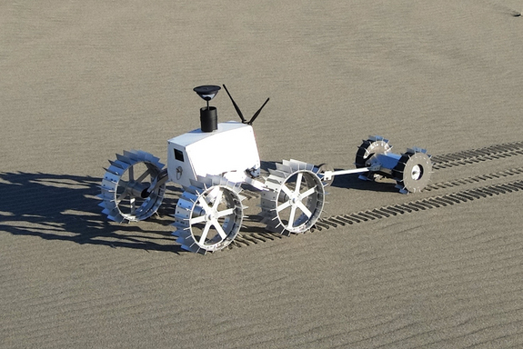 Engineering models of the dual rover system including the four-wheeled Moonraker and the two-wheeled Tetris rovers undergoing field testing at the Nakatajima Dune, Hamamatsu, Shizuokain, Japan, in late 2013.