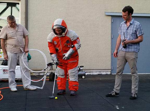 NASTAR space training center director Brienna Henwood puts a golf ball while wearing a Final Frontier Design spacesuit during the Brooklyn, New York-based company's Spacesuit Experience launch party atop a Brooklyn Navy Yards rooftop on Aug. 28, 2014.