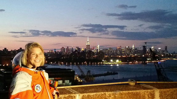 NASTAR space training center director Brienna Henwood, clad in a Final Frontier Design spacesuit, poses for photos with the New York City skyline as a backdrop during Final Frontier Design's Spacesuit Experience launch party on Aug. 28, 2014. The Brooklyn-based Final Frontier Design's Spacesuit Experience allows customers to wear its third-generation spacesuit under pressure, try out golf and a flight simulator, while learning how spacesuits work. The experience costs about $400.