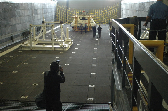 The Orion test article, a boilerplate version of the spacecraft with an unfinished interior, is seen in the well deck of the USS Anchorage. During recovery tests, the rear of the ship opened and allowed seawater to flood the well-deck area. The capsule was then floated out into the sea and recovered by Navy divers and smaller boats.