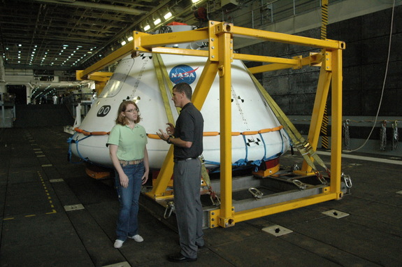 Seen next to the Orion test article are Brandi Dean, NASA spokesperson, and Jeremy Graeber, the NASA test director. The boilerplate Orion test article is basically an unfinished shell with the hatch and maneuvering thrusters merely painted on.