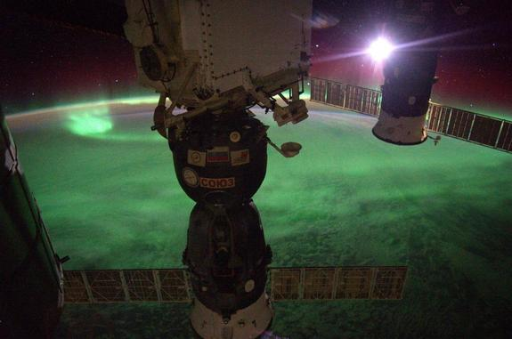 The moon shines to the left of a Soyuz capsule in this image of auroras below the International Space Station posted by Alexander Gerst on Sept. 3, 2014.