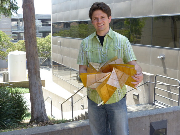 NASA engineer Brian Trease holds the prototype of the origami-inspired solar panel arrays.