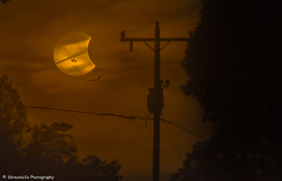 Photographer Shreenivasan Manievannan in South Carolina captured this view of the partial solar eclipse of Oct. 23, 2014 through fog and power lines, revealing an ethereal view of the event and giant sunspots on the sun.
