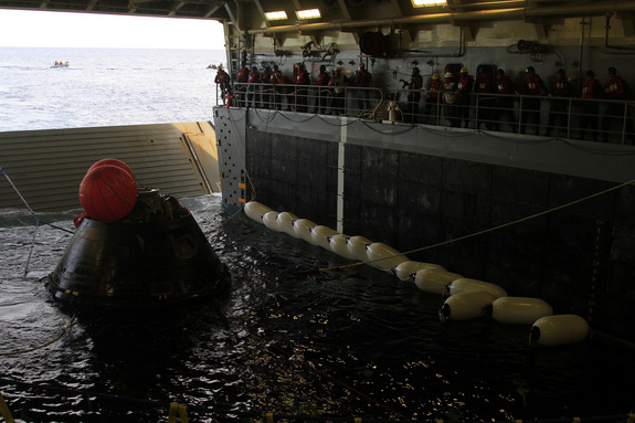 NASA's Orion space capsule is towed into the well deck of the USS Anchorage Navy ship during recovery efforts after the spacecraft's splashdown in the Pacific Ocean on Dec. 5, 2014.