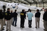 National Transportation Safety Board investigators are seen with Virgin Galactic's WhiteKnightTwo, the carrier plane for the SpaceShipTwo spacecraft, at the private spaceflight company's hangar in Mojave, California.
