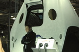 SpaceX CEO Elon Musk poses with the firm's manned Dragon V2 spacecraft during an unveiling event at the company's headquarters in Hawthorne, California on May 29, 2014.