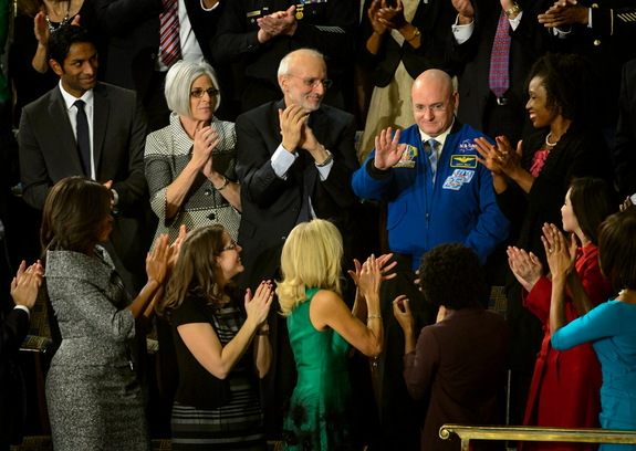 NASA astronaut Scott Kelly stands as he is recognized by President Barack Obama, while First lady Michelle Obama, front left, and other guests applaud, during the State of the Union address on Capitol Hill in Washington, Tuesday Jan. 20, 2015.