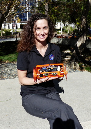 Carolyn Parcheta, a postdoctoral fellow at NASA's Jet Propulsion Laboratory in Pasadena, California, poses with the robot VolcanoBot 2, which will explore the inside of Hawaii's Kilauea volcano in March 2015.