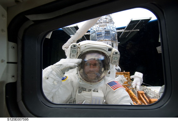 NASA astronaut Michael Good salutes during a spacewalk to upgrade the Hubble Space Telescope on May 15, 2009 during the space-based observatory's final servicing mission, STS-125.