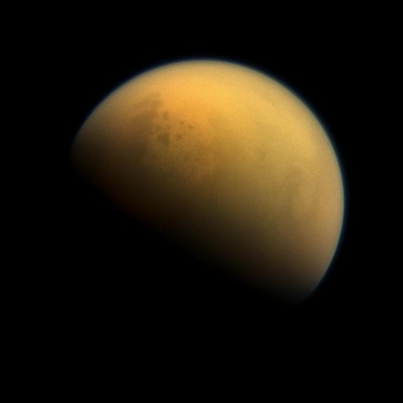 Saturn's largest moon Titan has a thick, smoggy atmosphere and is home to vast lakes of liquid methane, which are visible in this image as darker blotches in the moon's upper right. Titan's largest sea is called the Kraken Mare.