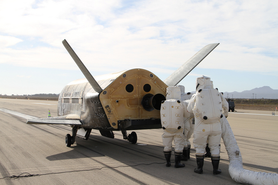 A recovery team processes the U.S. Air Force's X-37B space plane after the robotic spacecraft's successful landing at Vandenberg Air Force Base in California on Oct. 17, 2014. The touchdown marked the end of the X-37B's third space mission.