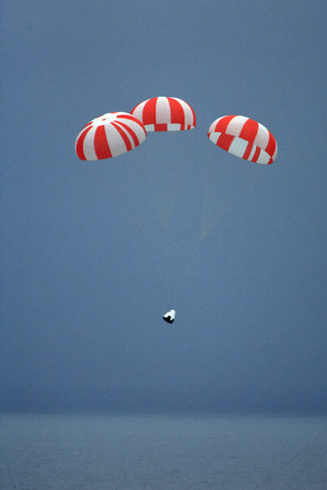 A SpaceX Dragon crew capsule prototype parachutes down to an ocean landing after a launch abort system test from Cape Canaveral Air Force Station, Florida on May 6, 2015. Riding aboard was a human-shaped dummy.