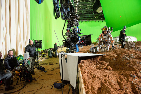 Mars On A Soundstage?  Or a soundstage on Mars? Actor Matt Damon concentrates on lonliness while surrounded by many film crew members.
