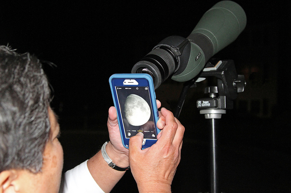 Imelda Joson demonstrates how the afocal projection technique is done using an iPhone 6 and the Swarovski spotting scope that she uses for birdwatching. This is the exact setup used to capture the accompanying photo of the first-quarter moon.
