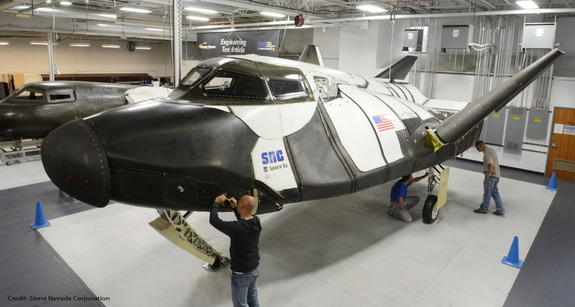 Technicians with the Sierra Nevada Corp. inspect the sub-orbital version of the Dream Chaser vehicle, which the company says would continue the legacy of NASA's shuttle program.