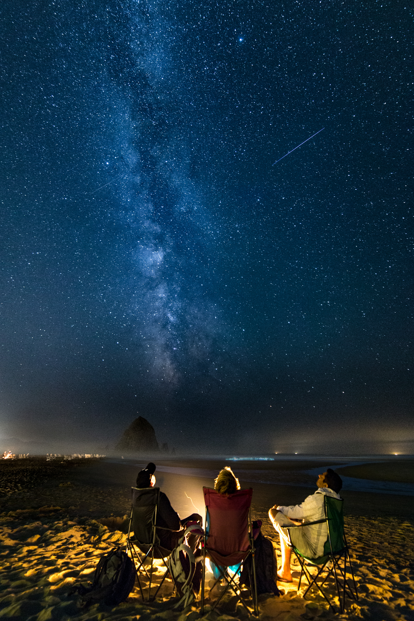 Under the Starry Sky: Trio Watches Meteor Shower in Stunning Photo