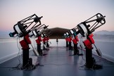 The MEarth-South telescope array, located on Cerro Tololo in Chile, searches for planets by monitoring the brightness of nearby small stars. This photograph shows the array, comprising eight 40cm telescopes, at twilight.