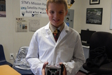 A student from St. Thomas More Cathedral School holds the STMSat-1 cubesat.