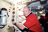 STS-92 commander Brian Duffy adds the patch for the 100th space shuttle mission to the International Space Station's wall in 2000.