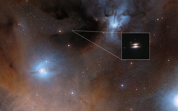 The young star 2MASS J16281370-2431391 lies in the Rho Ophiuchi star formation region, about 400 light-years from Earth. It is surrounded by a protoplanetary disk of gas and dust that is seen nearly edge-on from Earth; the disk's appearance in visible-light images has led to its being nicknamed the Flying Saucer. The main image shows part of the Rho Ophiuchi region; an enlarged close-up infrared view of the Flying Saucer from the Hubble Space Telescope is shown as an insert.