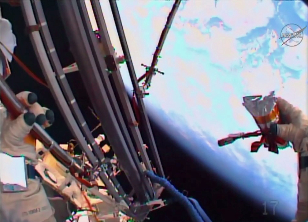 Russian Spacewalkers Maintain Experiments, Launch Ceremonial Flash Drive Into Space